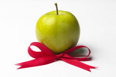Green apple and red ribbon bow royalty free stock photo