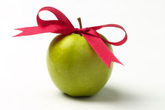 Green apple and red ribbon bow Royalty Free Stock Photography