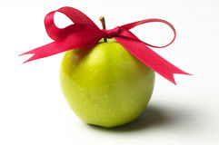 Green apple and red ribbon bow Stock Photo