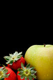 A green apple and red strawberries Royalty Free Stock Image