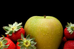 Green apple and red strawberries on black Royalty Free Stock Images