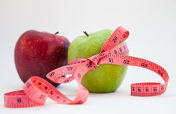 Green apple with red tape measure. Neutral background Royalty Free Stock Photography