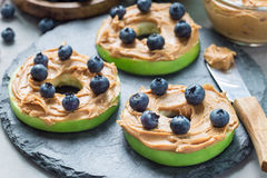 Green apple rounds with peanut butter and blueberries on slate board, horizontal. Healthy sandwich. Green apple rounds with peanut butter and blueberries on Stock Photos