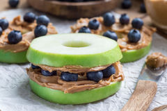Green apple rounds with peanut butter and and blueberries on wooden table, horizontal. Healthy sandwich. Green apple rounds with peanut butter and and stock images