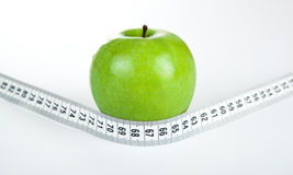 Green apple with a ruler Stock Photography