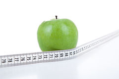 Green apple with a ruler Stock Images