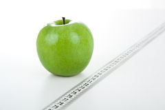 Green apple with a ruler Stock Photos