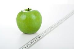 Green apple with a ruler Stock Photos