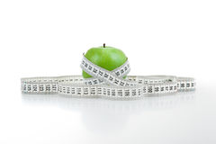 Green apple with a ruler Royalty Free Stock Images