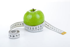 Green apple with a ruler Royalty Free Stock Photo
