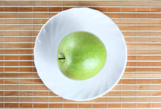 Green apple on the saucer Stock Photos
