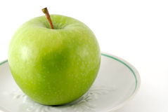 Green apple on a saucer. Isolated Royalty Free Stock Photo