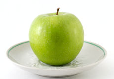 Green apple on a saucer. Isolated Royalty Free Stock Image