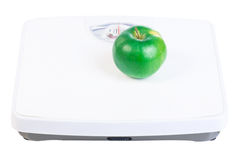 Green apple on the scales Stock Photo