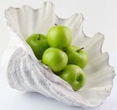 Green Apple in a seashell. On white back ground Stock Image