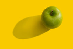 Green apple. With shadow over yellow background Royalty Free Stock Images