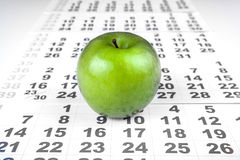 Green apple on sheets of wall calendar Stock Images