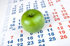 Green apple on sheets of wall calendar Royalty Free Stock Photography