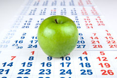 Green apple on sheets of wall calendar Royalty Free Stock Photos