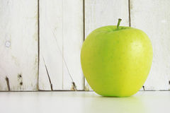A green apple on a shelf against a white wooden wall Royalty Free Stock Image