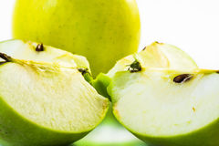 Green apple sliced in four pieces and an apple on a white background Stock Photo