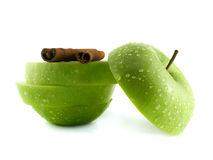 Green apple slices with cinnamon pods. (white background). Fresh diet fruit (water drops). Healthy fruit with vitamins Stock Images