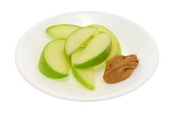 Green apple slices on dish with peanut butter Stock Image
