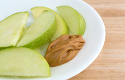 Green apple slices on dish with peanut butter table top Royalty Free Stock Photos