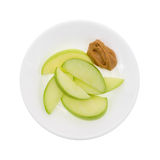 Green apple slices on dish with peanut butter top view Royalty Free Stock Image