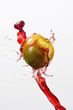 Green apple and splash of red juice on white.  Stock Image