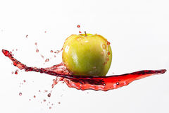 Green apple and splash of red juice on white background.  royalty free stock photo