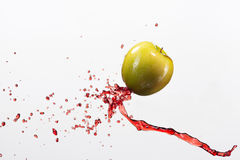 Green apple and splash of red juice on white background. Green apple and splash of red juice on white background Royalty Free Stock Photo