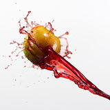 Green apple and splash of red juice on white background. Green apple and splash of red juice on white background stock image