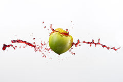 Green apple and splash of red juice on white background. Green apple and splash of red juice on white background Royalty Free Stock Photography