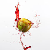 Green apple and splash of red juice on white background. Green apple and splash of red juice on white background Royalty Free Stock Photos