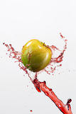 Green apple and splash of red juice on white background. Green apple and splash of red juice on white background Stock Images
