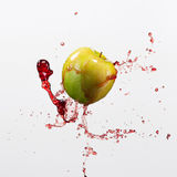 Green apple and splash of red juice on white background. Green apple and splash of red juice on white background Stock Photos