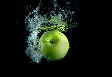 Green apple with splashes. Green apple on black background with splashes Royalty Free Stock Images