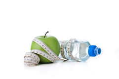 Green apple and sport bottle with measuring tape Stock Photo