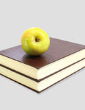 Green apple on stack of book isolated Stock Images