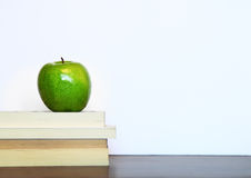 Green apple and stack of books with white copyspace Stock Images