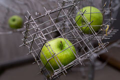 Green apple in a steel cage. Close-up Stock Photo