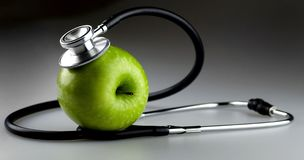 Green Apple with Stethoscope on Gray Background royalty free stock image