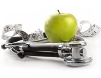 Green apple with stethoscope on white Stock Image