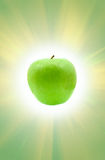 Green apple and sun. Green apple on rendered sun background royalty free stock image