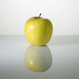 Green apple on a surface with reflection. Green elastic apple on a surface with reflection Stock Images