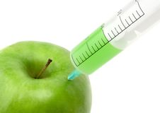 Green apple with syringe inser Royalty Free Stock Photos