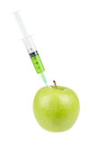 Green apple with syringe inserted Royalty Free Stock Photo