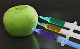Green apple with syringes Stock Photos