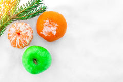 Green apple and tangerines on the snow. Christmas tree branch in the sun rays. Stock Photo